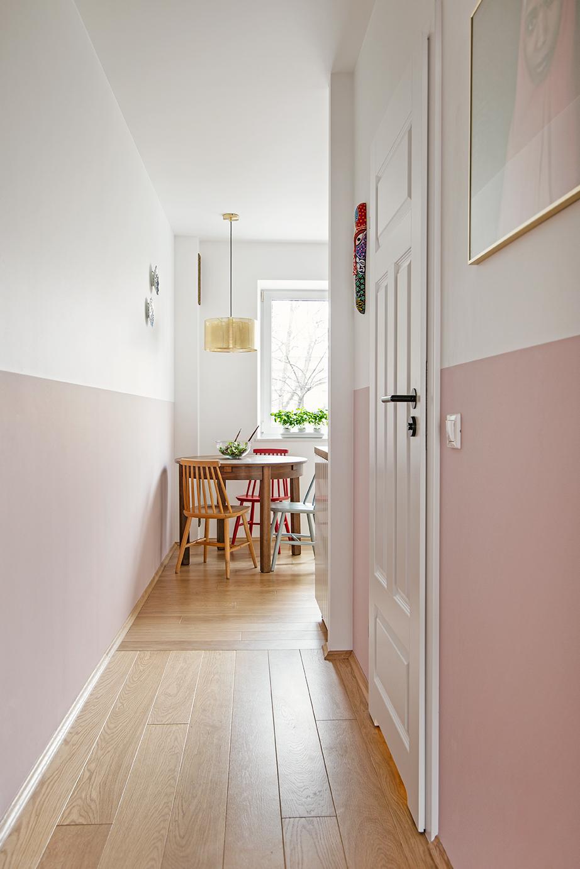 Klimatyczne mieszkanie na Nowolipiu widok z salonu na kuchnię różowa lamperia